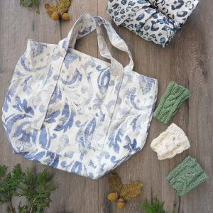 Hand Sewn market bag in blue and white print with two leopard print bags rolled up.